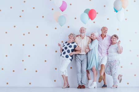 Happy older people smiling and standing with colorful balloons at the New Years Eve party photo