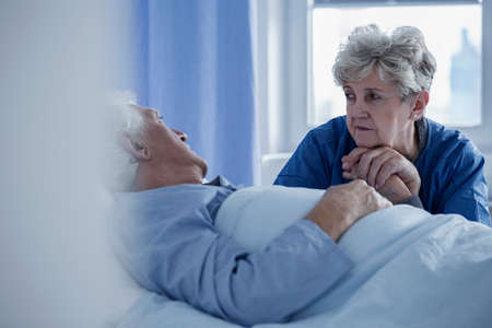 Senior woman holding the hand of a sick man lying in a hospital bed Stock Photo