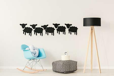 Kopierter Puff zwischen blauem Schaukelstuhl und hölzerner Lampe gegen die Wand mit Aufklebern der schwarzen Schafe im Wohnungsinnenraum Standard-Bild - 94924508
