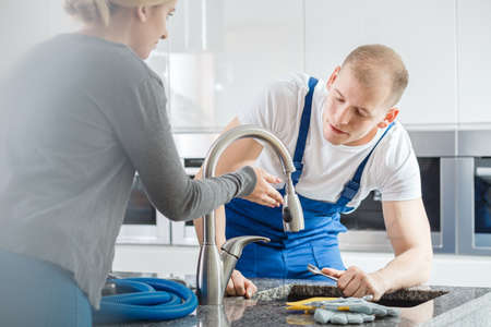 Housewife showing faucet glitch to a plumber in blue overalls