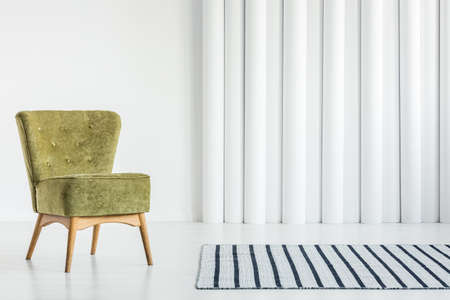 Green chair next to patterned carpet in bright living room interior with white tubes