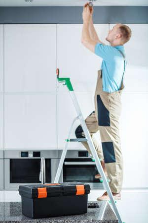 はしごの上に立って、台所の照明を修復するプロの電気技師