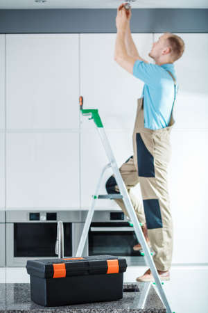 Professional electrician standing on a ladder and repairing lighting in the kitchen Фото со стока