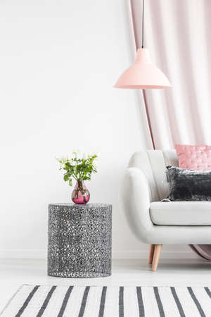Pink vase with flowers on metal table next to beige settee with cushions in pastel living room interior with patterned carpet and lamp