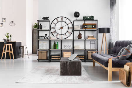 Laptop on black table and wooden dark sofa in manly flat interior with round clock on the wall and stools at kitchen island Editorial