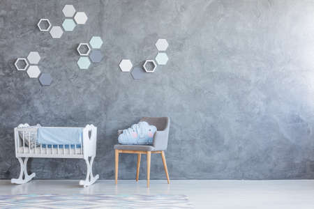 White cradle and grey chair standing against an empty wall in a nursery room interior