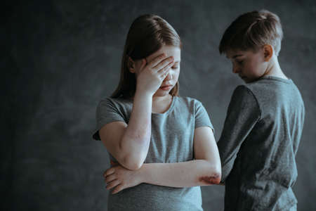 Depressed injured girl and sad boy against grey background. Children abducted for ransom