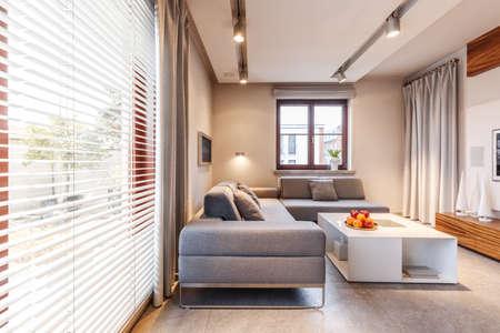 Szara narożna kanapa i biały stół w beżowym wnętrzu salonu ze światłami i oknem