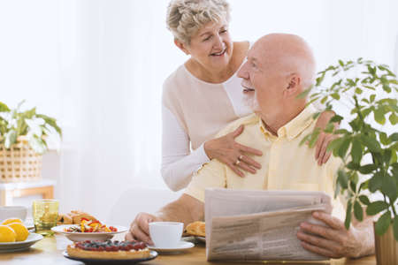 Elderly woman hugging her smiling husband reading newspaper during breakfast time