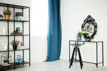 White flowers on dressing table with decorative mirror in sophisticated interior with blue curtain