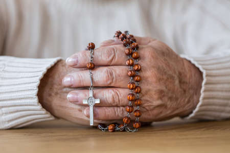 Close-up of senior's hands holding a red rosary with silver cross Foto de archivo