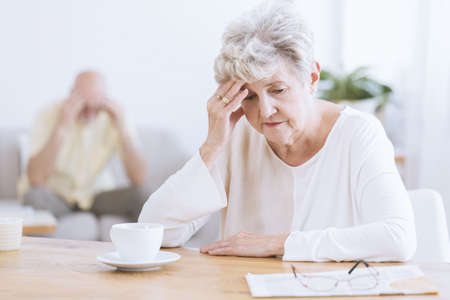 Sad senior woman sitting at a table after a quarrel with her husband Banco de Imagens - 95117812