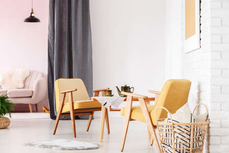 Wooden yellow armchairs at table in living room interior with dark drapes, basket and sofa in the background Standard-Bild