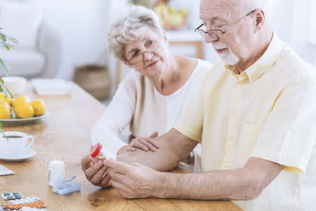 Worried wife supporting sick husband taking pills for hypertension