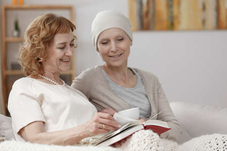 Mother reading a book to her smiling daughter suffering from cancer