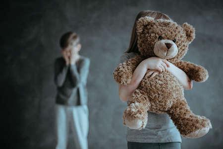 Na pierwszym planie dziecko trzymające misia w tle zazdrosnego, płaczącego brata Zdjęcie Seryjne