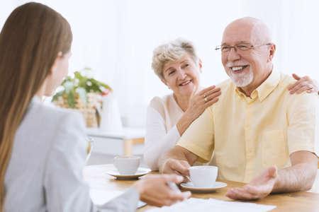 Figlia in visita a genitori anziani. Donna senior che beve tè con il marito felice