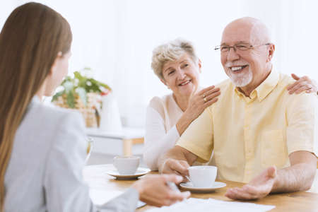 Daughter visiting elderly parents. Senior woman drinking tea with happy husband