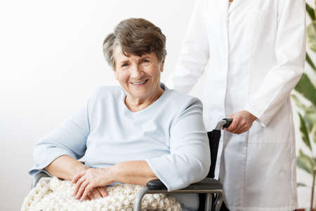 Caregiver and smiling disabled senior woman in a wheelchair
