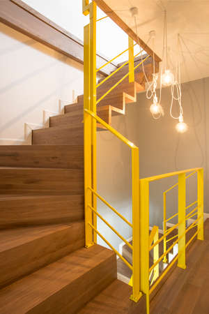 Lights in cozy loft interior with yellow railings of wooden stairs