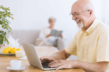 Smiling, excited grandfather using laptop and drinking tea Standard-Bild