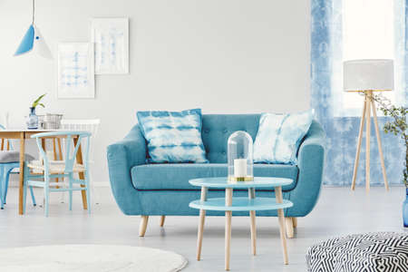 Candle on blue round table in front of a sofa with patterned cushions in flat interior with wooden lamp and posters on white wall Reklamní fotografie - 96890938