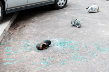 Broken glass, shoe and car parts on the street after car crash