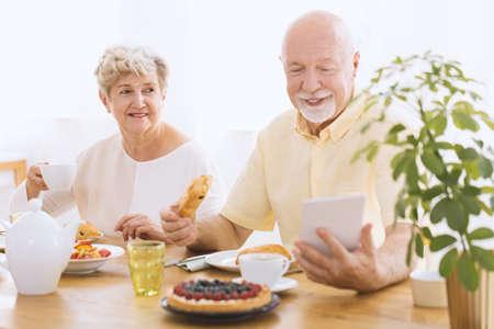 Happy elderly couple eating breakfast together. Senior man reading news using tablet.