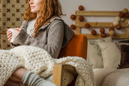 Red-haired woman drinking hot tea while sitting on bed with knit blanket during winter