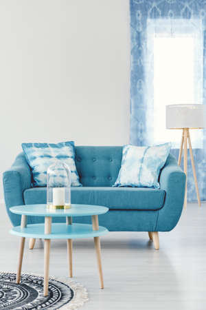 Candle on blue round table in living room interior with turquoise settee with patterned pillows against white wall with copy space 版權商用圖片
