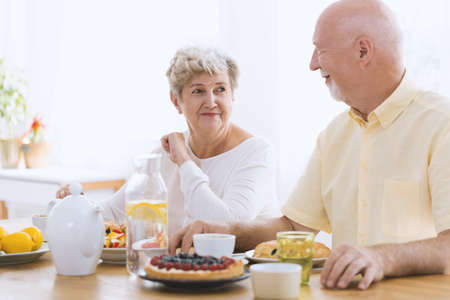 Happy couple of seniors looking at each other while eating breakfast and drinking tea Standard-Bild