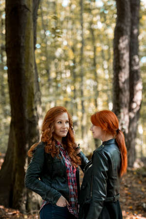 Vertical photo of red-haired sisters enjoying a walk in the forest Standard-Bild