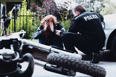 Policeman interrogating a motorcyclist injured in a car collision