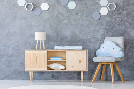 Wooden cupboard and chair with a cloud-shaped pillow in a baby room interior with honeycomb decoration on the wall