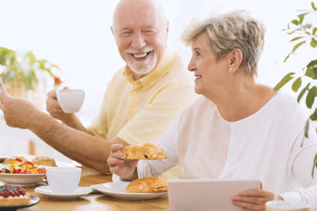 Happy grandmother eating breakfast and using tablet with her smiling husband