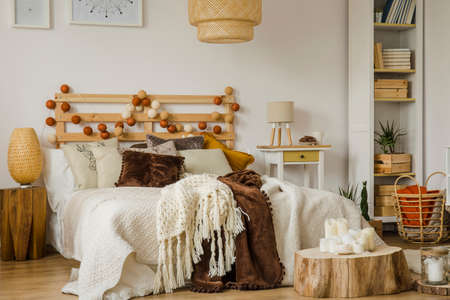 Lamp on wooden stool next to bed with cotton balls and knit blanket on bed in boho style bedroom interior Standard-Bild