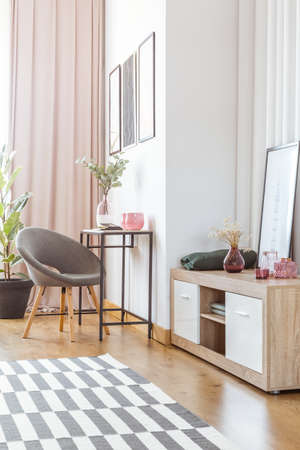 Grey armchair and flowers on wooden cupboard in cozy living room interior with pink curtain and patterned carpet