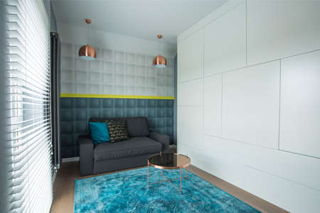 Metal lamps above dark sofa with pillows in blue living room interior with round table on carpet