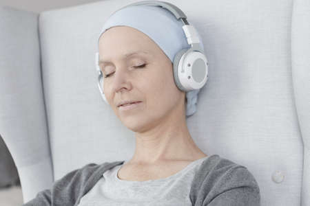 Close-up of relaxed woman with headphones on. Dealing with breast cancer concept.