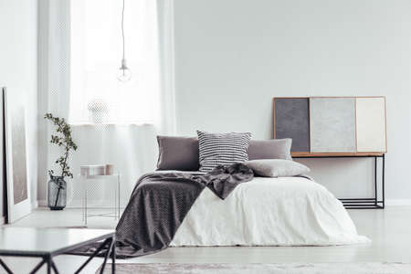 Decorative pillow with houndstooth pattern placed on the bed in white bedroom interior with window and simple lamp