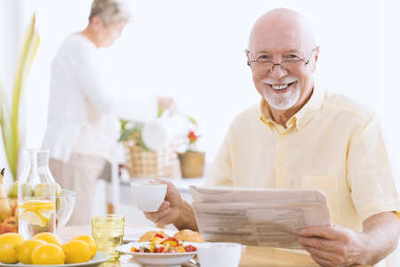 Smiling senior man reading a newspaper and drinking tea in the morning 写真素材