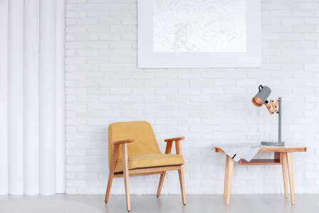 Wooden, yellow armchair next to a table with lamp against white brick wall with silver painting in dining room interior Standard-Bild