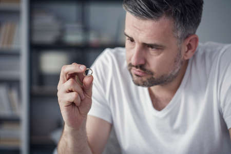 Sad man looking at his wedding ring after a divorce case Stock Photo
