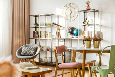 Gold round clock on the wall and telescope on the shelf in living room interior with grey armchair and heathers on dining table Standard-Bild