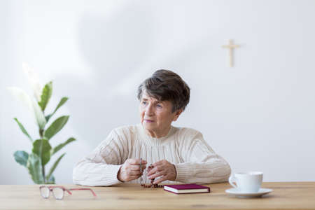 Religious elderly woman full of faith praying with a rosary at a table with bible