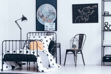 Clock on black chair and knot pillow on bed in astronomic bedroom interior with posters of moon and astronaut
