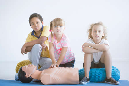 Multicultural group of children practicing chest compressions on a medical dummy during lesson 版權商用圖片