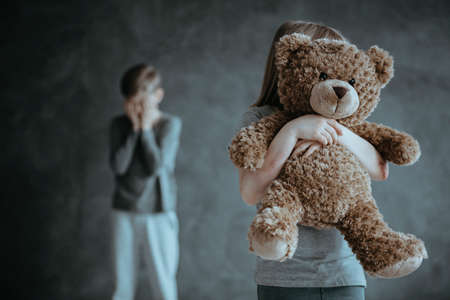 In the foreground kid holding a teddy bear in the background jealous crying brother Stock Photo