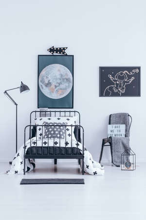 Chair with blanket and bed against white wall with moon and astronaut poster in bedroom interior with lamp