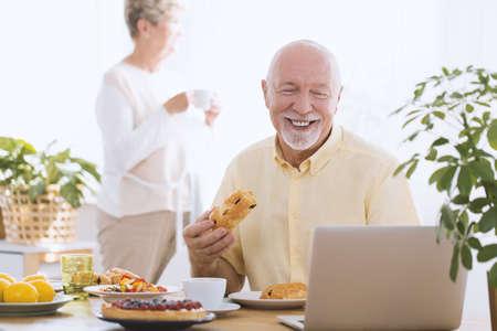 Smiling elderly man eating cake while using a laptop in the morning
